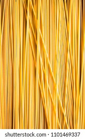 Uncooked whole wheat spaghetti italian pasta background, selective focus. Pasta pattern. Food background.
