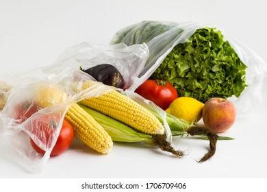 Nicht gekocht, frisches Gemüse und Obst in Plastiksäcken auf weißem Hintergrund mit Kopienraum.