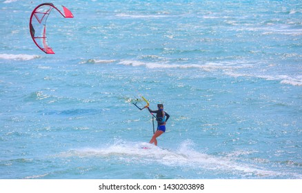 Undefined girl rides a kite -  Kitesurfers on the Gokova beach in Mugla. Gokova beach is most popular places in Turkey for kitesurfing.