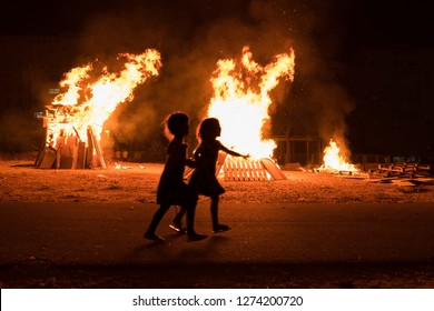 Undefined little jewish religious girls do bonfire at Jewish holiday of Lag Baomer