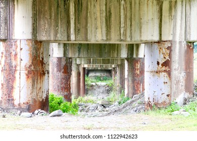 Under a abandoned viaduct pier with rusty pillar and rain mark grungy surface. Just like some kind of transporting door connect to some mysterious place.