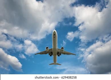 under a big jet plane on blue cloudy sky background