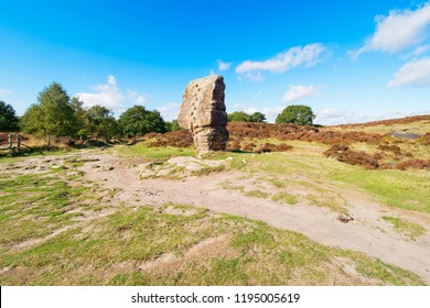 Under a blue lae summer sky a path winds round the Cork Stone ancient monolith in the Derbyshire Dales