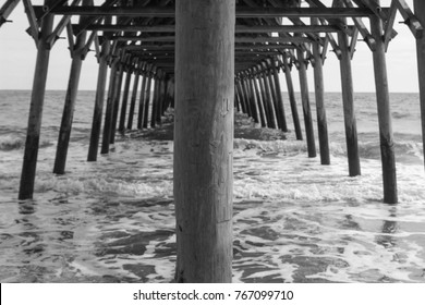 Under the boardwalk (pier) in black and white with calm waters. Taken at Garden City Pier in South Carolina