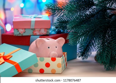 Under a Christmas tree in a holiday box we lay a piggy bank. A gift, a symbol of the new year. An unusual photo.