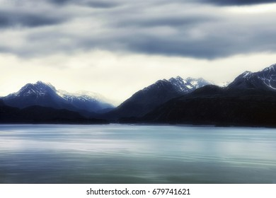 Under cloudy skies reflecting off of Kachemak Bay and hoovering over the Kenai Mountain Range in Homer Alaska.  The image has been enhanced to reflect the dream like mood of the minimalist landscape