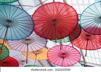 Under colorful Chinese umbrellas. Open with wood handles.