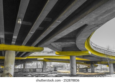 Under a concrete road bridge with yellow pillars