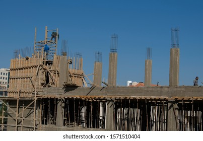 An under construction building with wood plates and iron beams, stanchions, pillars for new storey, a wall of bricks not covered with cement by Architectural Coatings, and building materials