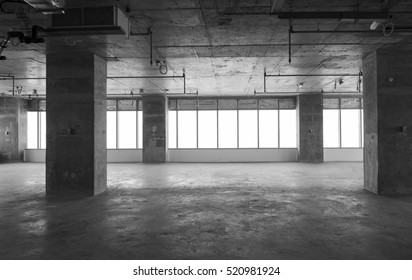 An under construction office building interior. A huge hall with panoramic windows being constructed.