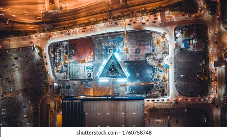 Under construction site, crane, parking lot, and car traffic transportation in Asian city at night. Drone aerial top view. Industrial business or civil engineering technology concept