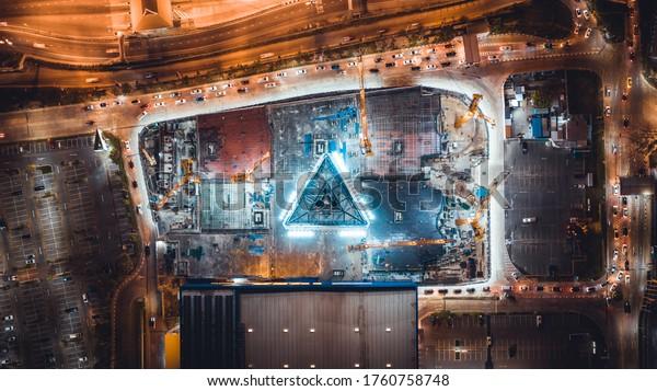 Unter Baustelle, Kranich, Parkplatz und Autoverkehr in asiatischen Stadt nachts. Draufsicht aus der Drohne. Konzept der Industrie- und Tiefbautechnik