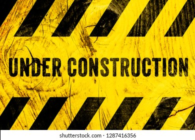 Under construction warning sign text with yellow black stripes painted on wood wall plank texture wide background. Concept do not enter the area, caution, danger, construction site.