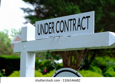 Under contract sign on wooden post. Real estate business.