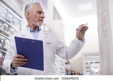 Under control. Low angle of mature pensive male pharmacist standing in profile while using clipboard