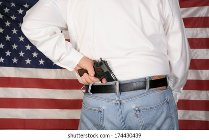 A under cover police officer or concerned citizen has a .45 caliber Pistol Concealed in his back waistband as he stands in front of the American Flag. The perfect image for your 2nd amendment rights