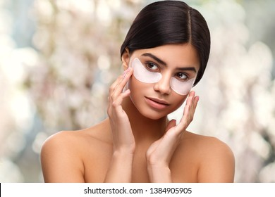 Under eye patches for dark circles and puffiness. Taking care of her skin. Pretty woman using eye patches spending time at home. Daily pampering routine. Modern cosmetics. Eye patches concept