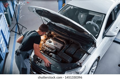 Under the hood. Man in grey uniform repairs white automobile indoors.