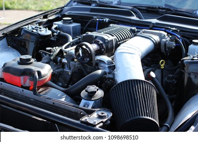 Under the hood of a sports car: a powerful gasoline engine with a supercharger and a small air filter.