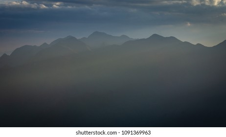 Under the light of the sunset, mountains outlined and blurred by the haze of the Brazilian winter. Dark and dark tones in the blue setting and suvez rays of sun entering the mist.