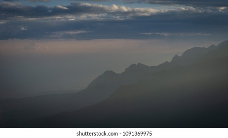 Under the light of the sunset, mountains outlined and blurred by the haze of the Brazilian winter. Dark and dark tones in blue placement.