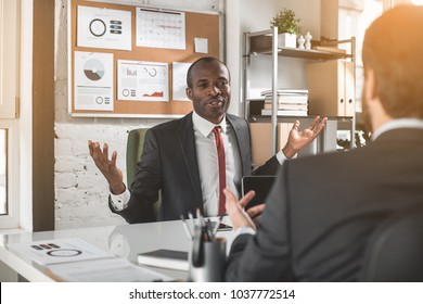 Under negotiation. Portrait of professional young african businessman in suit is sitting at table and discussing project. He is looking at his partner who sitting in front of him and gesticulating
