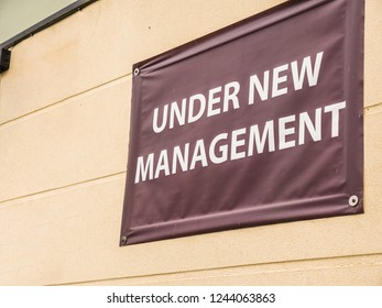 under new management sign banner on wall ouside shop in england