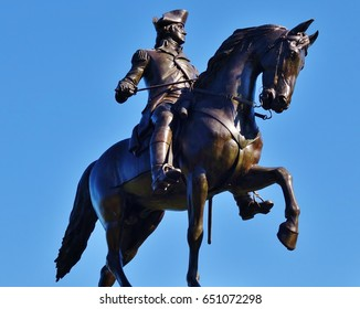 Under a nice blue sky, in the Boston, Massachusetts Public Garden, this is the colossal equestrian bronze statue of George Washington, sword in hand, on a horse with its front legs in the air.