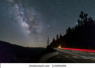 Under a night sky with the Milky Way shining brightly, automobile taillights streak through the scene and into a tunnel on Big Oak Flat Road in California's Yosemite National Park.