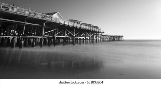 Under Pacific Beach Pier with sunset beam rays shining through pier pillars. San Diego, California