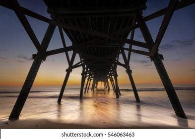 Under the pier at Surf Side Beach, Myrtle Beach, South Carolina before sunrise