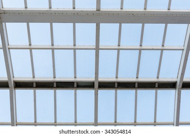 Under the roof. Glass panel roof with white battens under bright blue sky