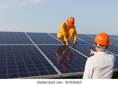 Under the sun, there are two engineers checking solar cells.