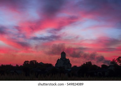 Under the sunset sky landscape of Ukrainian Orthodox Church in the village of ancient Ukrainian Carpathian on a hill near the ancient Galic on the background of flaming sunset