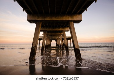 Under the Tybee Island pier in Southern Georgia United States at sunset on the Atlantic Ocean