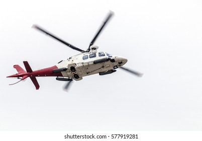 Under view of airborne helicopter isolated against white overcast sky
