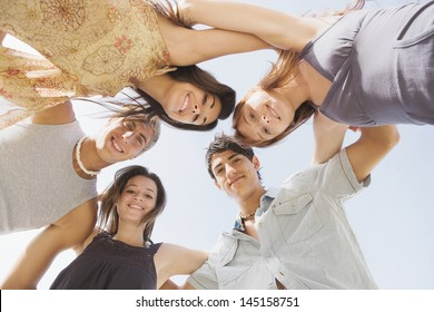 Under view of a group of five teenagers friends looking down at the camera with their arms around each others shoulders against a sunny sky while on vacation during the summer break.