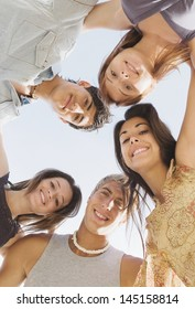 Under view of a group of five teenagers friends looking down at the camera and smiling with their arms around each others shoulders against a sunny sky while on vacation during the summer break.