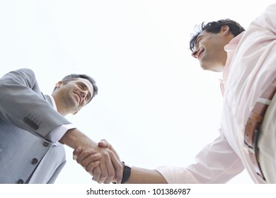 Under view of two businessmen shaking hands, with the sky behind them.