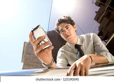 Under view of a young aspirational businessman using a smart phone while leaning on a banister outside a modern glass office building in the city.