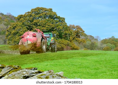 Underbarrow, Cumbria/ United Kingdom - October 23 2019 : A tractor  muck spreading in a field in the Lake District