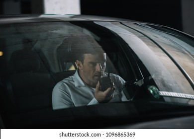 undercover male agent doing surveillance and using talkie walkie in car