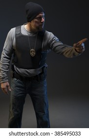 Undercover Special Agent with weapon pointing on dark studio background.