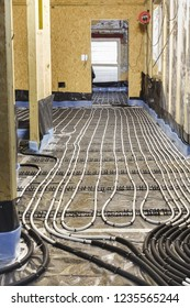 Underfloor heating water pipes installation to subfloor of a house under construction