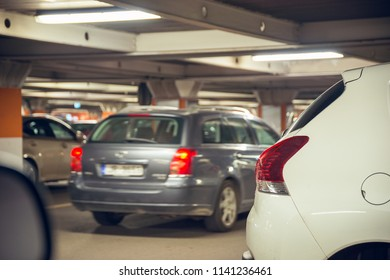 Underground car parking. Different cars standing parked at underground parking at shopping mall.