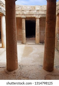 an underground chamber at the tombs of the kings in paphos cyprus with old eroded sandstone columns surrounding a dark empty doorway and blue sky