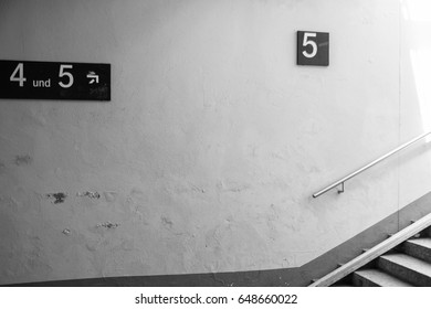 Underground crossing at the station, stairs and signs with different numbers.