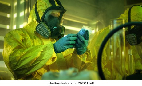 In the Underground Drug Laboratory Clandestine Chemist Wearing Protective Mask and Coverall Holds Bag with Blue Meth Amphetamine. His Team Synthesises Illegal Substances in the Abandoned Building.
