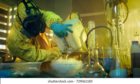 In the Underground Drug Laboratory Two Clandestine Chemists Covered in Protective Coveralls and Gas Masks Mix Chemicals to Synthesise Drugs. They Work in the Abandoned Building.