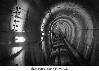 Underground facility with a big tunnel leading deep down. Abstract architecture black and white concept background. Soft and select focus.